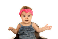 Cute baby girl sitting in a brown chair Stock Image