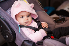 Cute baby girl sitting in a child seat Royalty Free Stock Image