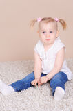 Cute baby girl sitting on floor Stock Photos