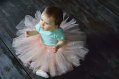 Cute Baby girl sitting on the floor in nice skirt. Top view. Stock Photos