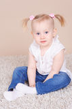 Cute baby girl sitting on floor Stock Photo