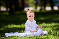 Cute baby girl sitting on the green grass in the city park at warm summer day. Stock Photo