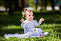 Cute baby girl sitting on the green grass in the city park at warm summer day. Stock Photography