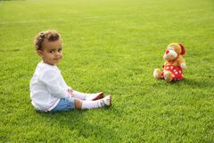 cute baby girl sitting on green grass with her t Stock Photography