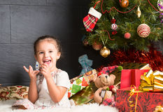 Cute  baby girl sitting on rug and laughing in Christmas interio Stock Photography