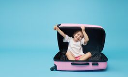 Cute baby girl sitting in a suitcase and waiting for summer vacation after quarantine. Pointing to the side.