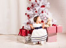 Cute  baby girl sitting under Christmas tree Royalty Free Stock Image