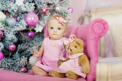 Cute baby girl sitting under christmas tree in room stock image
