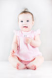 Cute baby girl sitting and wearing a pink dress Royalty Free Stock Images