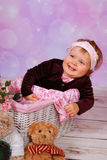 Cute baby girl sitting in white basket Stock Photography