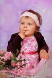 Cute baby girl sitting in white basket Stock Photo