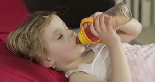 Cute baby girl sleeping on cozy bed at home and drinking juice from bottle. Pretty, little girl sleeping in morning light. Close-up portrait of child naps stock video footage