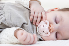 Cute baby girl sleeping over white bedcover Royalty Free Stock Images