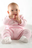 Cute baby girl smiling with thumb in her mouth Royalty Free Stock Photography