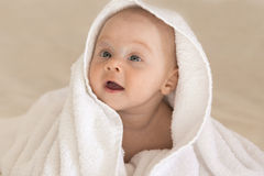 Cute baby girl smiling in white towel. Funny face Royalty Free Stock Photo
