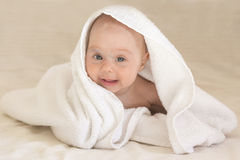 Cute baby girl smiling in white towel. Funny face Stock Photo