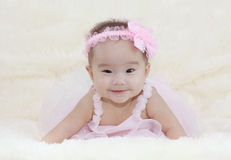 Cute baby girl on a soft white carpet. In a beautiful pink dress Stock Photo