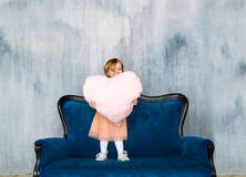 The cute baby girl stand on a sofa and holds heart pillow in hands. Stock Image