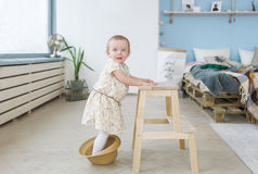 The cute baby girl stand on a straw hat and leans on a wooden chair Royalty Free Stock Image