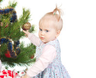 Cute baby girl standing near the Christmas tree. Isolated on white Royalty Free Stock Images