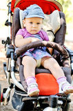 Cute baby girl in stroller Stock Photos