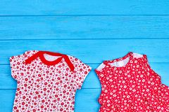 Cute baby girl summer wear. Infant girl printed bodysuit and dress on blue wooden background, copy space. Casual clothing for infant baby girl Stock Photos