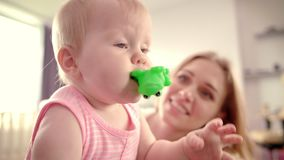 Cute baby girl with toy. Infant baby looking aroung. Happy loving family. Cute baby girl with toy. Toddler gnawing green toy frog. Little child eating rubber toy stock footage