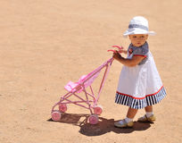 Cute baby girl with toy stroller Royalty Free Stock Photos