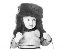 Cute baby girl trying fur hat Stock Photo