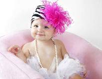 Cute Baby girl in tutu and hat. A 1 year old baby girl dressed up in a feather and zebra stripe hat, pearls and tutu Stock Image