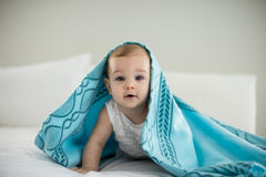 Cute baby girl under the blanket on bed Royalty Free Stock Photo