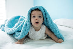 Cute baby girl under the blanket on bed Royalty Free Stock Photos