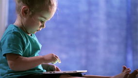 Cute baby girl use a Tablet PC, touches finger