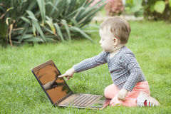Cute baby girl using a laptop Stock Photos