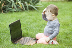 Cute baby girl using a laptop Stock Photo