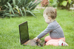 Cute baby girl using a laptop Stock Images