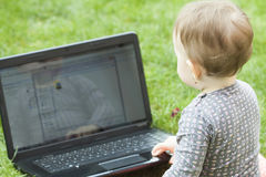 Cute baby girl using a laptop Stock Image