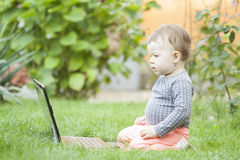 Cute baby girl using a laptop. In the garden Stock Image
