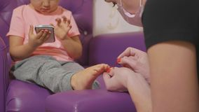 Cute baby girl using smart phone at pedicure procedure at beauty spa salon. Cute baby girl using smart phone at pedicure procedure at beauty spa salon in slow stock footage