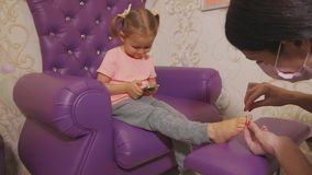 Cute baby girl using smart phone at pedicure procedure at beauty spa salon. Cute baby girl using smart phone at pedicure procedure at beauty spa salon in slow stock video