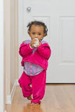 A cute baby girl walking with her bottle Royalty Free Stock Image