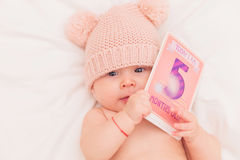 Cute baby girl wearing knitted bear hat holding a card royalty free stock images