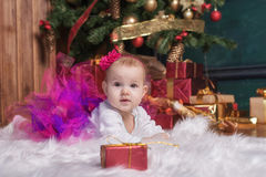 Cute baby girl wearing pink skirt and red headband, lying on white carpet near christmas trees. Christmas gifts. Stock Photos
