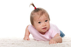 Cute baby girl on the white carpet Royalty Free Stock Image