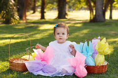 Cute  baby girl in white dress with Easter chocolate eggs in par Royalty Free Stock Photography