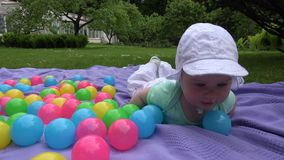 Cute baby girl with white hat crawl between colorful balls on plaid. 4K stock footage