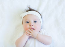 Cute baby girl in white shirt on white blanket with white bow Stock Photos