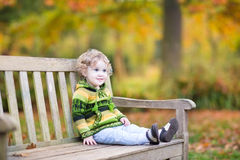 Cute baby girl on wooden bench in autumn park Royalty Free Stock Photo