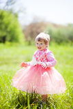 Cute baby girl 1-2 year old in fancy dress in the Park. Portrait of cute little cheerful girl outdoors on warm and sunny summer da Stock Image