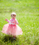 Cute baby girl 1-2 year old in fancy dress in the Park. Rejoice and clap their hands Stock Photos